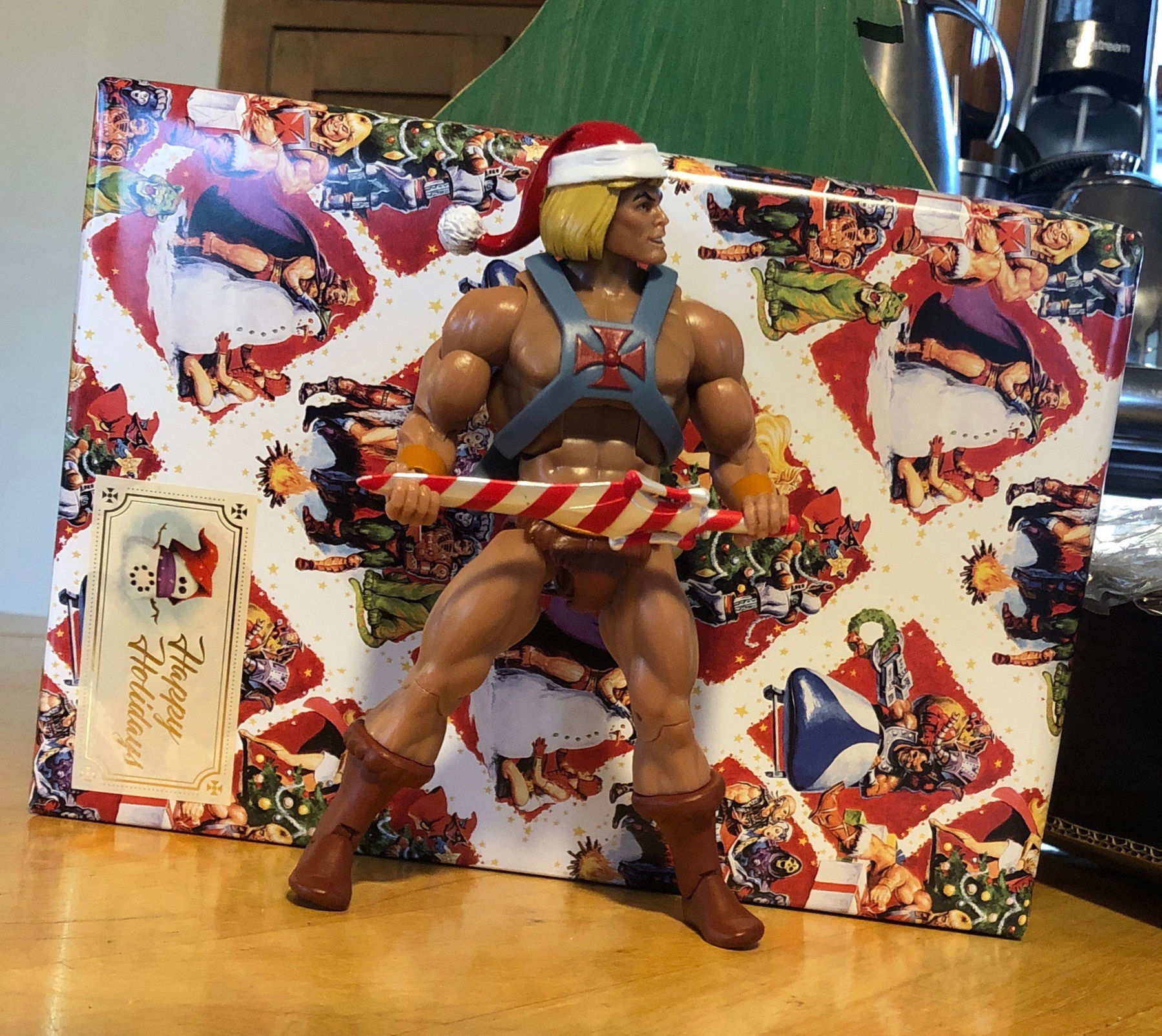 He-Man action figure wearing a Santa hat and holding a candy cane sword in his iconic stance. Behind him is a package wrapped in Masters of the Universe wrapping paper.